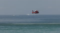 US Coast Guard Dolphin Helicopter over the water in search and rescue mode Stock Footage