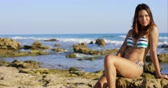Sexy young woman sitting on rocks at the seaside - stock footage