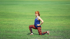 Young woman doing exercise on grass in the park Stock Footage