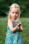 Adorable young girl holding grasshopper, curiosity and education concept Stock Photos