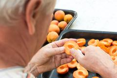 Anonymous man halving fresh homegrown apricots - stock photo