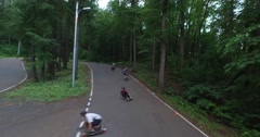 Longboard skating on the winding asphalt road in the forest Stock Footage