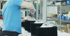 Worker in an assembly line for lighting fixtures Stock Footage