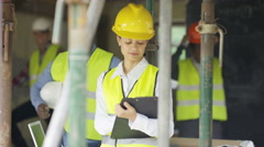 4K Portrait of worker at construction site writing notes on clipboard Stock Footage