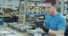 Medium Tracking shot of a worker in an electronics assembly line Stock Footage
