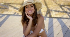 Smiling brown haired beauty sits on boardwalk Stock Footage