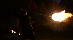 Fire show on the street with a guy who turns a ball of fire on chains Stock Footage
