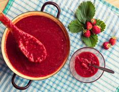 Homemade strawberry jam (marmelade) cooking. Large pot with hot jam Stock Photos