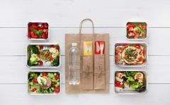 Healthy food take away in boxes, top view at wood - stock photo