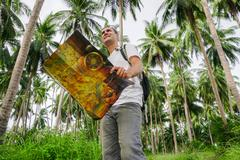 Young male traveler checking map in palm grove. - stock photo