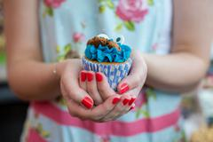 Woman in Floral dress holding cookie monster cupcake - stock photo