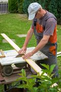 Carpenter working with electric buzz saw cutting wooden boards Stock Photos