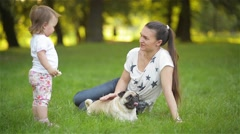 Mother and child playing with dog on a warm summer day, Mom with daughter Stock Footage