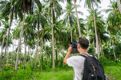 Young male traveler taking photo in palm grove. Stock Photos