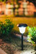 Small Solar Garden Light, Lantern In Flower Bed. Garden Design Stock Photos