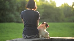 Happy young woman sit back with dog and looking at each other outdoors,  Stock Footage