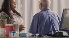 Nurse receiving medical history from senior male patient Stock Footage