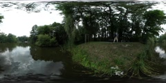 360Vr Video Man Gets on a Bicycle Riding by Alley Park Rippling Water Forest Stock Footage