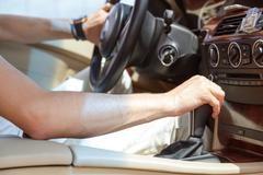 Driver man hand holding automatic transmission in car Stock Photos