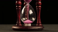 Hourglass in wooden stand. Pink sand. Black. Close up - stock footage
