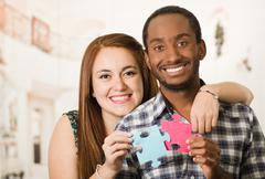 Interracial charming couple embracing friendly, holding up large puzzle pieces Stock Photos