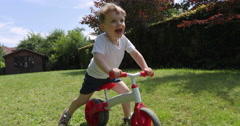 Toddler riding pushbike garden slow motion Stock Footage