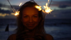Closeup of happy woman with sparkler fireworks on the beach at twilight. Stock Footage