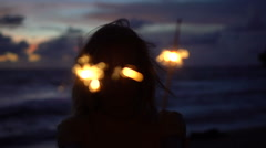 Closeup of happy woman with sparkler fireworks on the beach at twilight. - stock footage