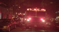 Fire truck with flashing siren lights standing in the city at night Stock Footage