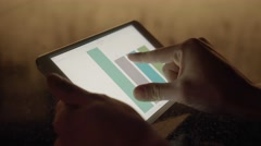 Hand zooming into business charts analyzing investment statistics on tablet Stock Footage