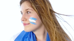 Girl with Argentinian flag on her face smiling, slow motion Stock Footage