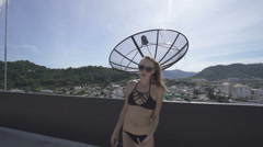 Sexy glamour woman wearing black swimwear posing on a rooftop in a sunny day.  Stock Footage