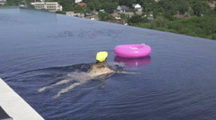 Woman swimming with inflatable ring in infinity rooftop pool on a sunny day. Stock Footage