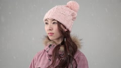 Young attractive Japanese woman in snowboard outfit under falling snow Stock Footage
