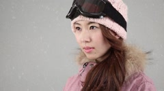 Young attractive Japanese woman in snowboard outfit under falling snow - stock footage