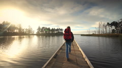 Young man hiking on dock on lake, Oregon Stock Footage