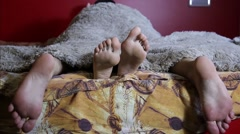 Two pairs of male and female feet seen from under the blanket. sleep together Stock Footage