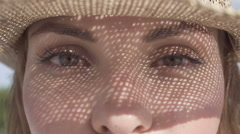 Eyes closeup of pretty girl with straw hat pattern shadow on her face. Stock Footage