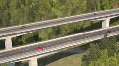 AERIAL: Cars and semi trucks driving on big highway viaduct and into the tunnel - stock footage