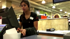 Woman paying Adidas pants at check out counter inside sport chek store Stock Footage