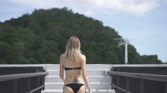 Back view of sexy blonde tatooed woman walking on a rooftop stairs over sky. Stock Footage