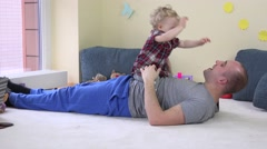 Lovely baby girl sits on dad stomach and embrace loving father - stock footage