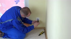 Worker man repair an electrical outlet in apartment Stock Footage