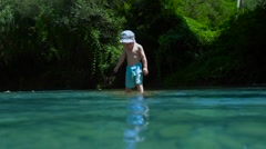 Beautiful Little Boy Throws Pebbles in a Mountain River - stock footage