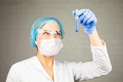 Female medical or scientific researcher with a test tube of clear solution in Stock Photos