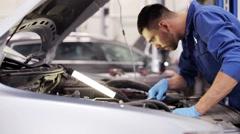 Mechanic man with lamp repairing car at workshop Stock Footage