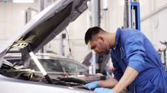 Mechanic man with wrench repairing car at workshop Stock Footage