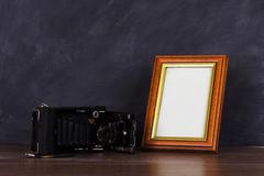 Vintage camera and frame against blackboard background - stock photo