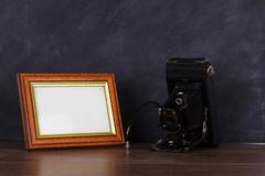 Vintage camera and frame against blackboard background - stock photo