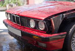 Front part of red car without wing with water drops on car wash Stock Photos